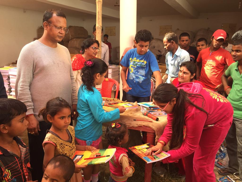DISTRIBUTING BOOKS AND STATIONERY TO POOR CHILDREN.